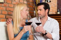 Pares atractivos que beben el vino rojo en restaurante o barra Imagen de archivo libre de regalías