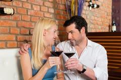 Pares atractivos que beben el vino rojo en restaurante o barra Fotografía de archivo libre de regalías