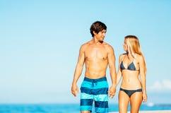 Pares atractivos que caminan en la playa tropical Foto de archivo libre de regalías