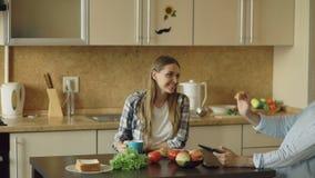 Pares atractivos que charlan y que desayunan en la cocina almacen de video
