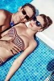 Pares atractivos que descansan por la piscina Foto de archivo libre de regalías