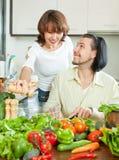 Pares atractivos que preparan una comida de verduras Imagen de archivo libre de regalías