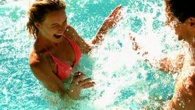 Pares atractivos que salpican en la piscina junto el días de fiesta almacen de video