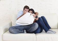 Pares atractivos que se divierten en casa que goza mirando la demostración de la película de terror de la televisión Imagen de archivo