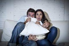 Pares atractivos que se divierten en casa que goza mirando la demostración de la película de terror de la televisión Foto de archivo libre de regalías