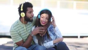 Pares atractivos que se divierten que escucha la música con los auriculares almacen de metraje de vídeo