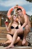 Pares atractivos que se relajan por la piscina Foto de archivo libre de regalías
