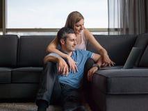 Pares atractivos usando un ordenador portátil en el sofá Imágenes de archivo libres de regalías