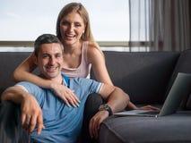 Pares atractivos usando un ordenador portátil en el sofá Fotografía de archivo