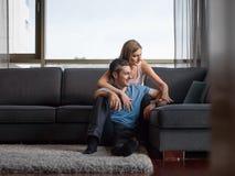 Pares atractivos usando un ordenador portátil en el sofá Imagen de archivo