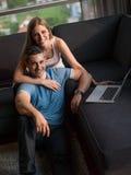 Pares atractivos usando un ordenador portátil en el sofá Imagen de archivo libre de regalías
