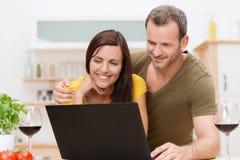 Pares atractivos usando un ordenador portátil en la cocina Imagenes de archivo