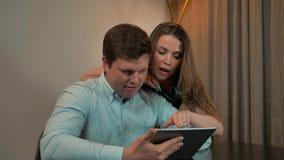 Pares atractivos, varón y hembra, practicando surf en la tableta en hogar metrajes