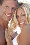 Pares atractivos y felices del hombre y de la mujer en la playa Foto de archivo