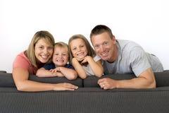 Pares atractivos y felices jovenes que presentan sentando en casa el sofá co imagen de archivo libre de regalías