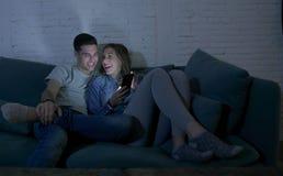 Pares atractivos y felices jovenes usando Internet app en el teléfono móvil que goza y que ríe junto sentando en casa la sala de  Imagenes de archivo