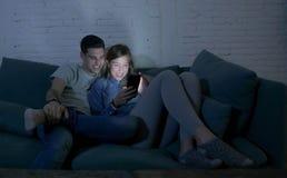 Pares atractivos y felices jovenes usando Internet app en el teléfono móvil que goza y que ríe junto sentando en casa la sala de  Fotografía de archivo