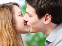 Pares atrativos de amantes que beijam-se lovingly em um sofá Fotos de Stock Royalty Free
