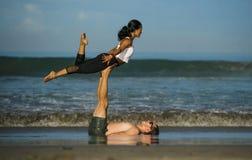 Pares atrativos e concentrados novos de acrobatas que praticam o equil?brio da ioga do acro e o exerc?cio da medita??o na praia b fotos de stock