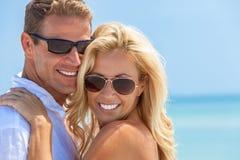 Pares atrativos felizes da mulher e do homem nos óculos de sol na praia Imagem de Stock Royalty Free