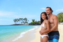 Pares atrativos felizes que relaxam na praia das férias fotos de stock royalty free
