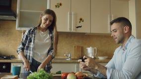 Pares atrativos na cozinha Equipe o jogo do jogo de vídeo no smartphone quando seu cozimento da amiga filme