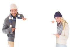 Pares atrativos na forma do inverno que mostra o cartaz Fotos de Stock Royalty Free