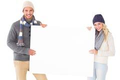 Pares atrativos na forma do inverno que mostra o cartaz Foto de Stock