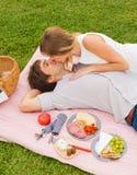 Pares atrativos no beijo romântico do piquenique da tarde Imagem de Stock