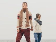 Pares atrativos novos em camisetas feitas malha em um penhasco na costa de mar Fotografia de Stock Royalty Free