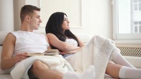 Pares atrativos novos felizes que sentam-se junto no sofá que fala, rindo e lendo um livro video estoque