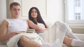 Pares atrativos novos felizes que sentam-se junto no sofá que fala, rindo e lendo um livro fotos de stock