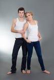 Pares atrativos novos nas calças de brim e nas camisas brancas Foto de Stock Royalty Free