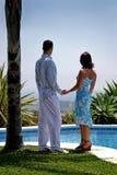 Pares atrativos novos nas mãos da terra arrendada do amor sob uma palmeira Imagem de Stock