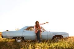 Pares atrativos novos que abraçam ao estar perto de um carro retro imagens de stock royalty free