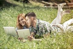 Pares atrativos novos que encontram-se na grama, olhando o portátil Fotos de Stock Royalty Free