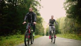 Pares atrativos que andam com bicicletas e água potável na floresta filme