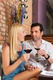 Pares atrativos que bebem o vinho vermelho na barra Fotografia de Stock Royalty Free