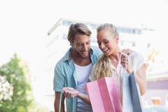 Pares atrativos que olham compras da compra Imagens de Stock