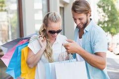 Pares atrativos que olham compras da compra Imagem de Stock