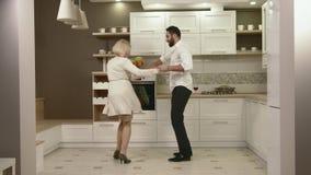 Pares atrativos que têm o divertimento que dança junto na cozinha video estoque