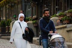 Pares azerbaijanos novos na maca Uma mulher em um hijab branco e um homem que leva um carrinho de crian?a com um beb? imagem de stock royalty free