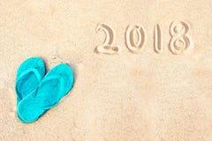 Pares azules de chancletas en la playa, 2018 escrito en la arena Imágenes de archivo libres de regalías