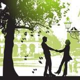 Pares bajo el árbol en parque de la ciudad Imagenes de archivo