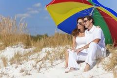 Pares bajo el paraguas colorido en la playa Fotografía de archivo libre de regalías