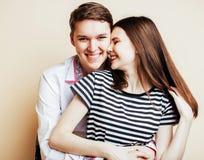 Pares bastante adolescentes de los jóvenes, individuo del inconformista con su sonrisa feliz de la novia y abrazo aislados en el  Fotos de archivo