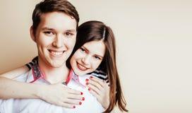Pares bastante adolescentes de los jóvenes, individuo del inconformista con su sonrisa feliz de la novia y abrazo aislados en el  Foto de archivo