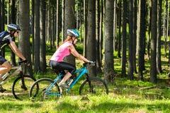 Pares biking desportivos nas madeiras Imagem de Stock Royalty Free