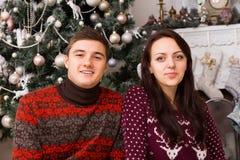 Pares blancos jovenes en Front Christmas Tree Foto de archivo libre de regalías