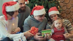 Pares bonitos alegres de la familia y sus amigos que se sientan con el bebé que da sus diversos presentes y que muestra luces almacen de metraje de vídeo